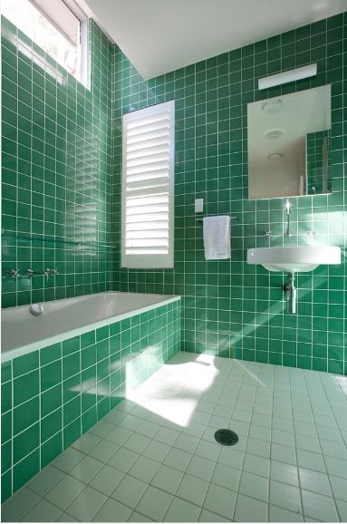 The green-tiled walls are paired with a white shuttered window above the head of the white tub inlaid with the same green tiles.
