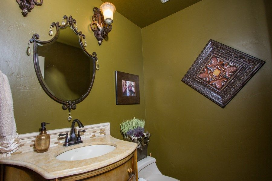 The earthy tone of the green textured walls of this bathroom is well paired by the elegant vanity mirror and its matching wall-mounted lamps.