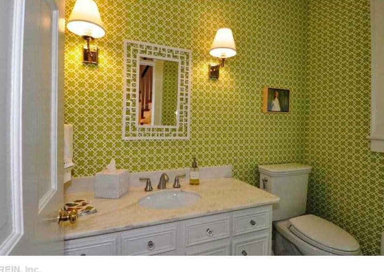 This bathroom dominated by walls covered in green patterned wallpaper that is brightened up by the wall-mounted lamps.