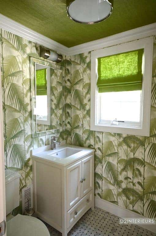 The green palm leaves covering most of the walls are the highlight of this bathroom that has a simple white vanity and mirror.