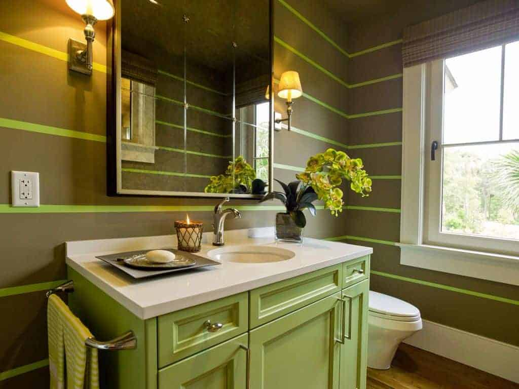 This airy bathroom has stylishly striped green walls that are complemented by a green vanity with white countertop.