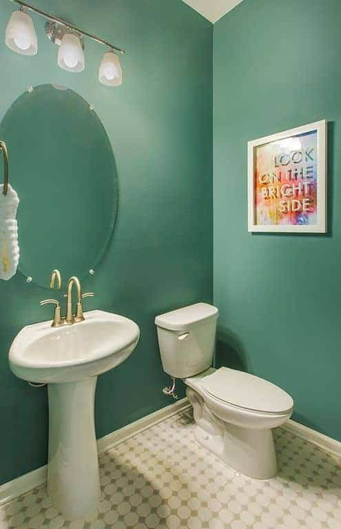 The blue-green walls of this bathroom are adorned with a wall-mounted framed inspirational poster over the toilet.