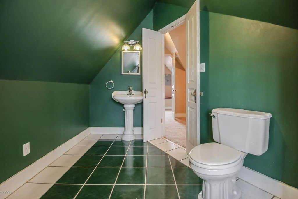 This is an attic bathroom with a green cathedral ceiling that extends to the walls and floor tiles. This makes the white sink and toilet stand out.