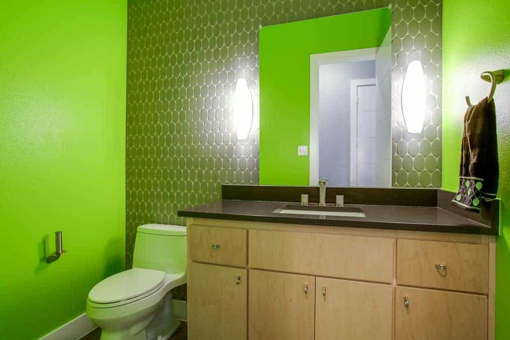 The wall behind the vanity mirror has dark gray patterns that match with the dark countertop and contrasts the green walls.