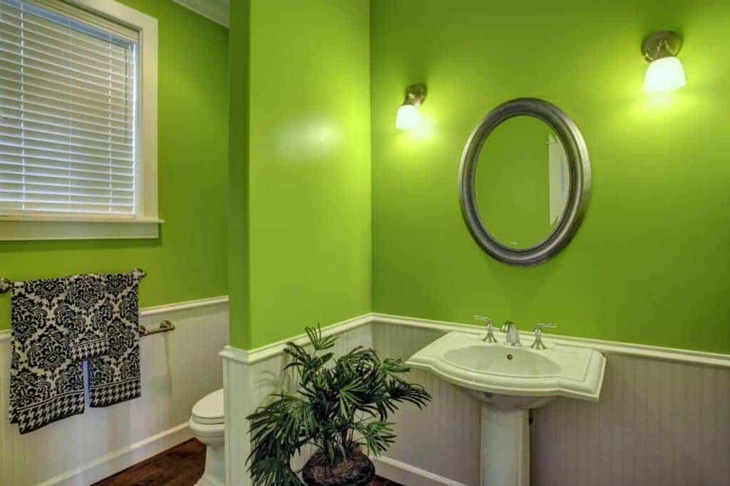 The charming green walls are adorned with an elliptical mirror flanked by wall-mounted lamps over the white wainscoting.
