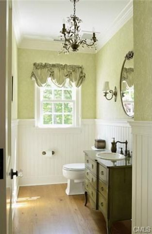 The light green walls are brightened by the window that emphasizes the dark iron chandelier and matching wall-mounted lamps.