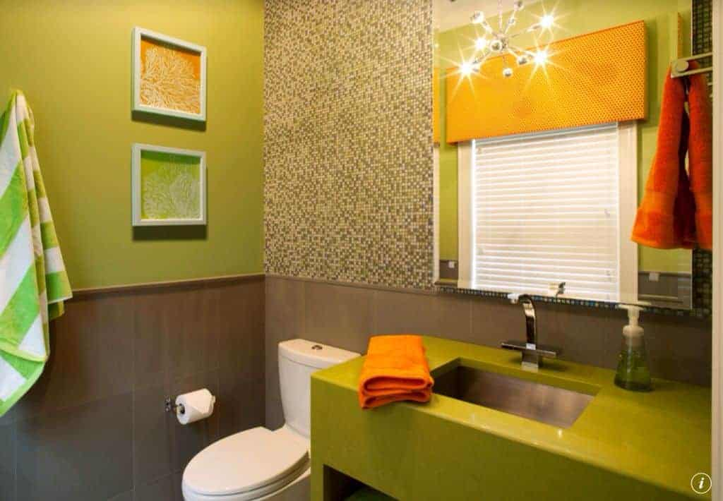 The charming sink area is colored green that matches with the walls adorned with a couple of wall-mounted artworks.