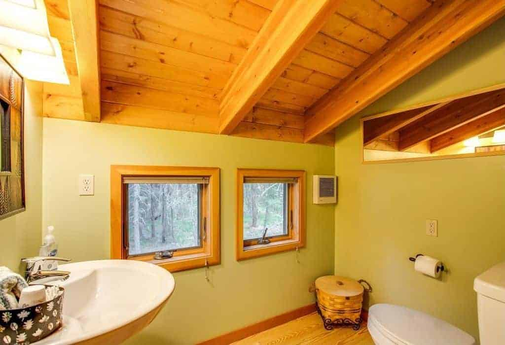 The wooden shed ceiling has exposed beams that match the hardwood flooring. This is a nice framing for the green walls.