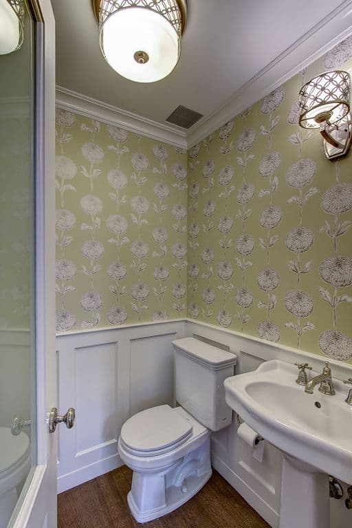 The walls of this bathroom are covered in light green wallpaper that has floral patterns complemented by chic flush mount light and a wall-mounted lamp.