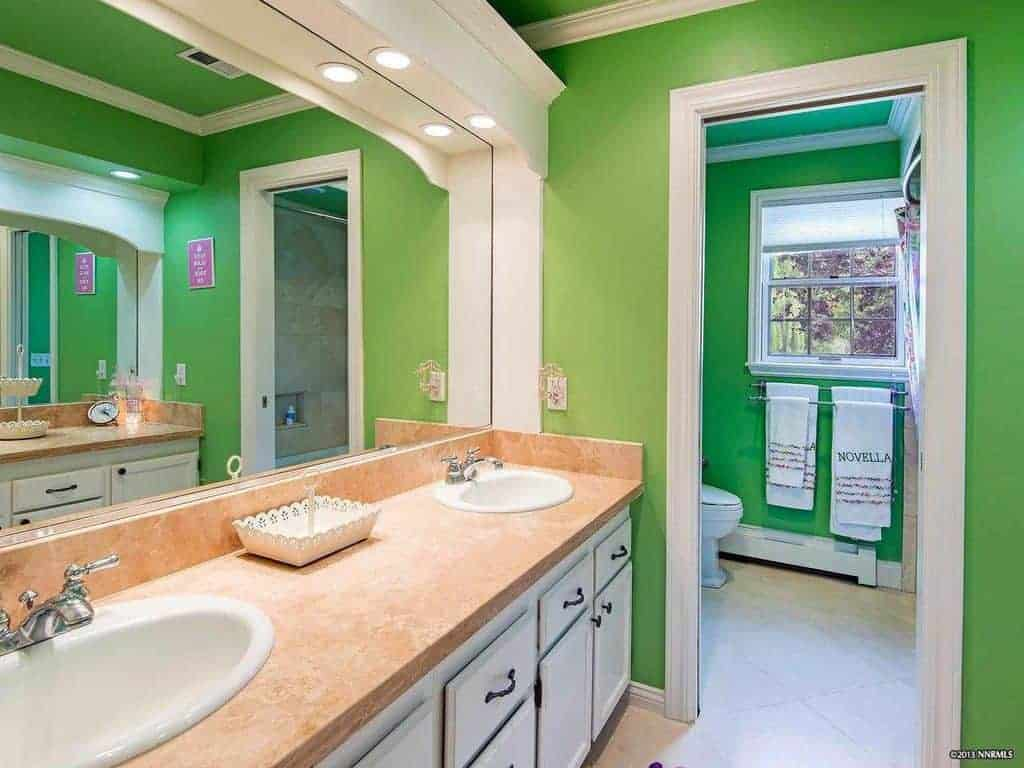 The green walls make the white structure of the vanity area stand out with its built-in pin lights shining down on the beige countertop.