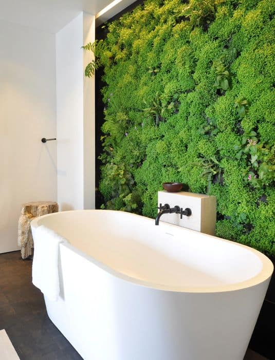 The wall that serves as a background for the freestanding bathtub is filled with plants, ferns, and moss for a wall that looks like it is alive.