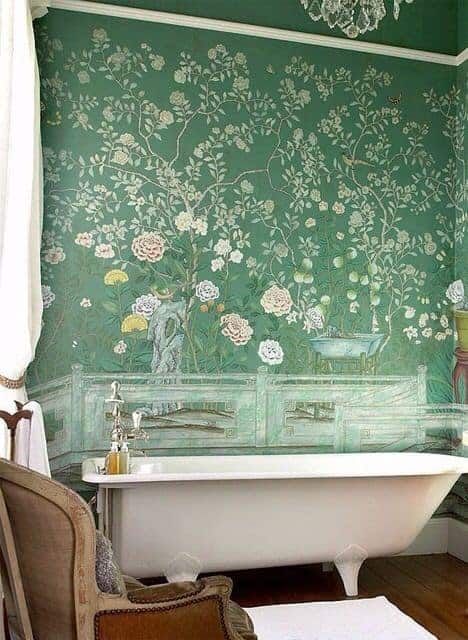 The freestanding bathtub is paired with a chic green wall covered with floral designs for a lovely chic aesthetic.