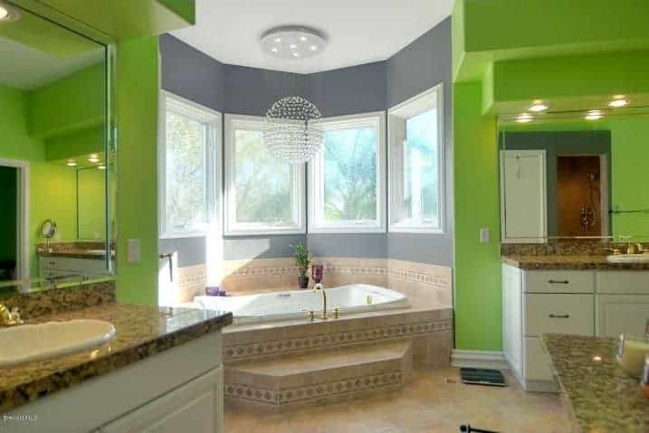 The vanity areas have green walls that flank the gray-walled alcove of the bathtub that is surrounded by windows.