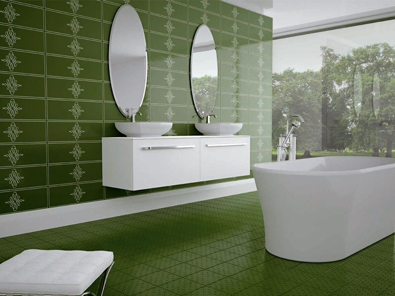 The dark green hues of the floor tiles match with the wall tiles that have an intricate and elegant design. This makes the pure white tub and vanity area stand out.