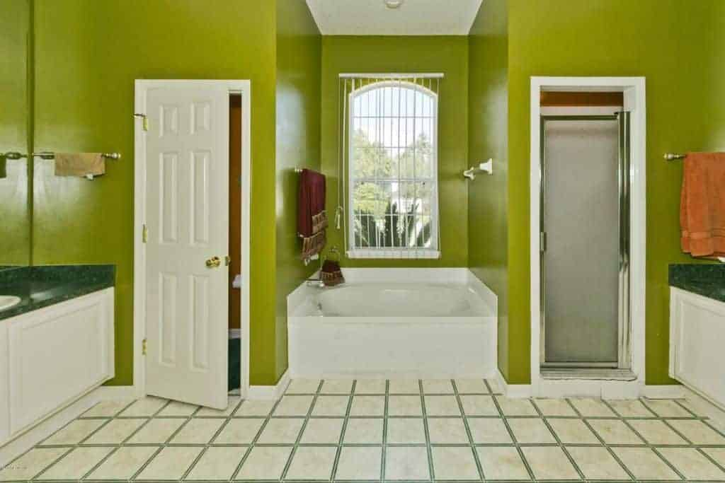 The sleek and unique green hue of the walls stands out against the white-tiled floors and bathtub that is inlaid into an alcove by the window.
