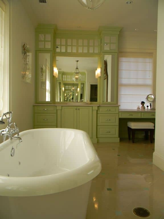 The white walls and beige flooring is dominated by a large green wooden structure that houses the vanity area.