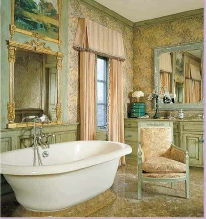 This chic bathroom has light green wainscoting paired with beige floral wallpaper that matches the cushions of the wooden armchair beside the bathtub.