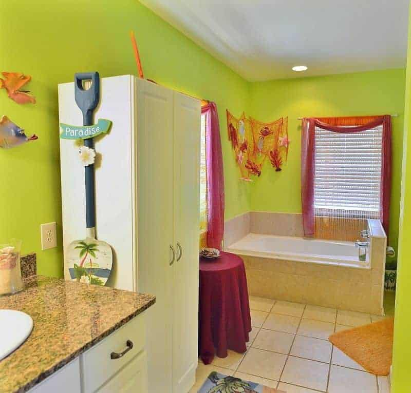 This avocado green bathroom has a homey feel to it with the various artworks and decors on the walls.