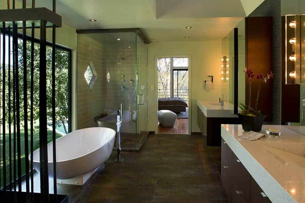 The freestanding bathtub is placed beside a huge glass window that brightens up the light green walls and ceiling.