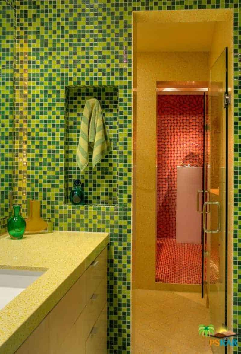 The walls of this bathroom have various shades of green placed in a seemingly random pattern that contrasts the beige flooring and countertop.
