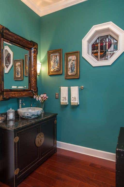 The blue-green walls are framed with white molding that blends with the white ceiling. The elegantly framed vanity mirror stands out against the pastel colors.