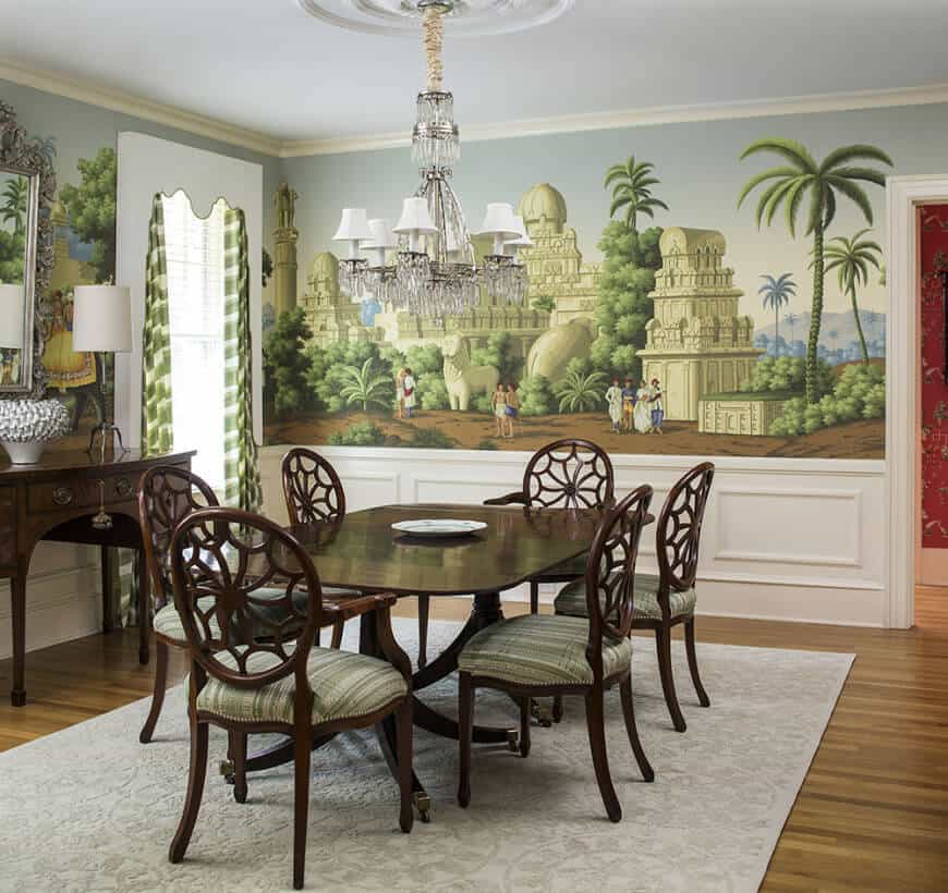 The walls of this formal dining room are adorned with murals of greenery that pairs well with the green patterns of the wooden chair cushions.