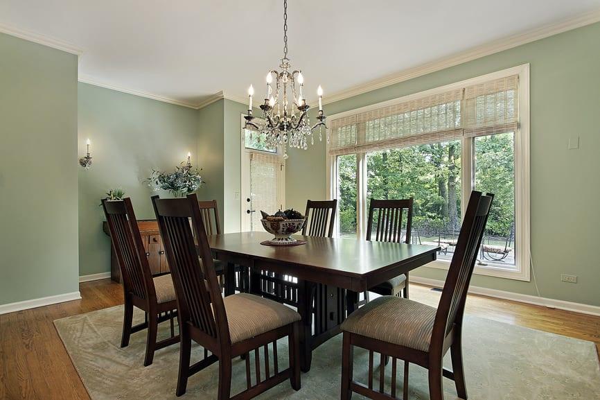 Light pastel green colors dominate the walls as well as a wide window that illuminates the dark wooden table and slat-backed chairs.