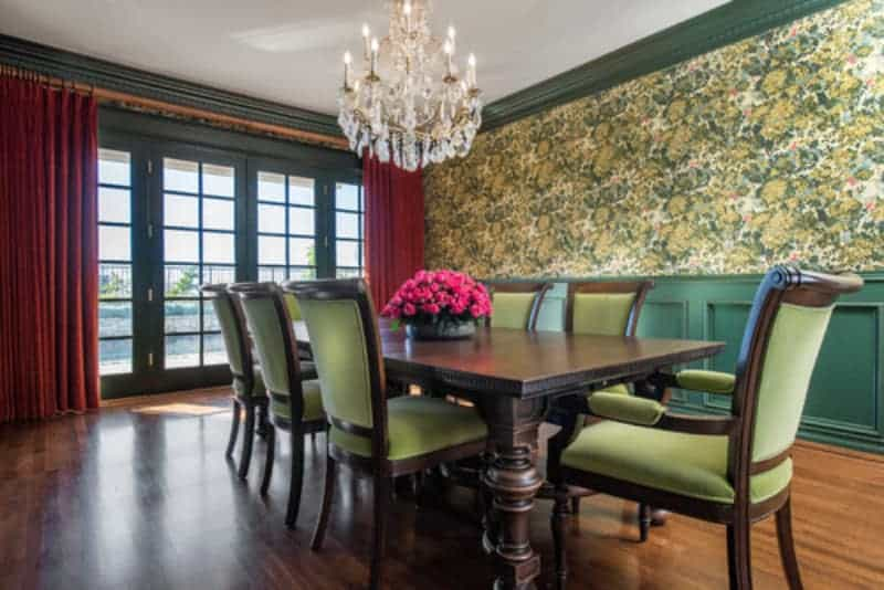 Natural light coming in from the French glass doors illuminate the hardwood flooring and green floral walls that match the green cushions of the dining chairs.
