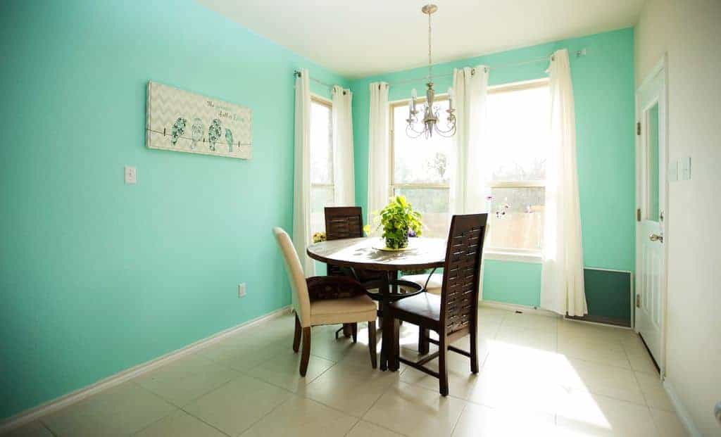The bright baby blue-green palette of the walls bring a homey feel to this simple dining room that has a round wooden table surrounded by wooden chairs.
