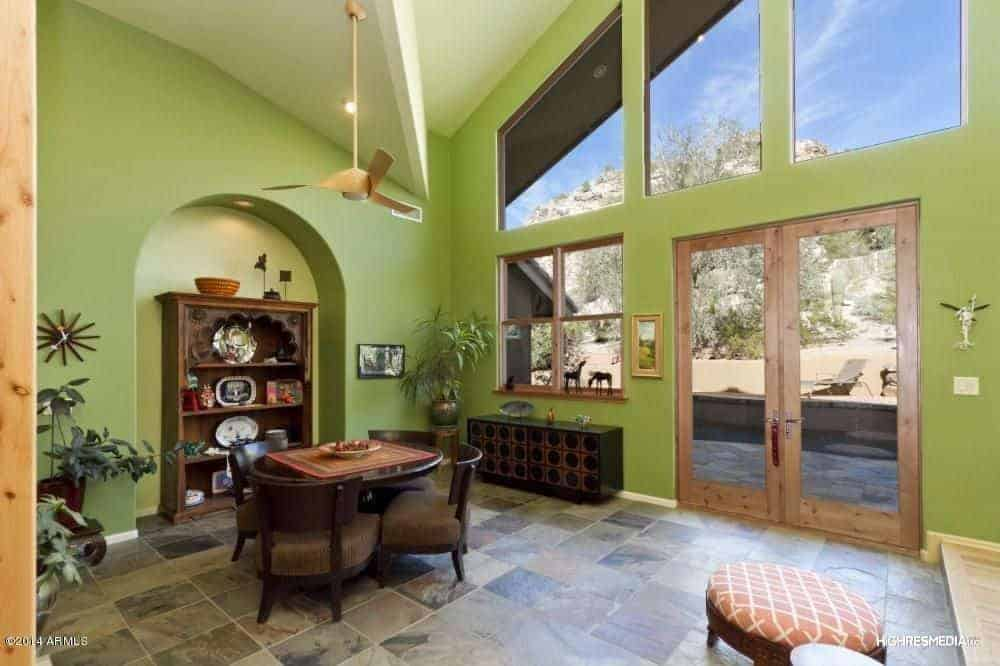 This is a simple dining area within a great room that has avocado green walls that has an arched alcove beside the round wooden table.