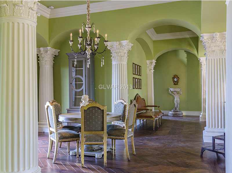 This is a spacious dining room that has avocado green walls and ceiling complemented by white greek pillars for drama.