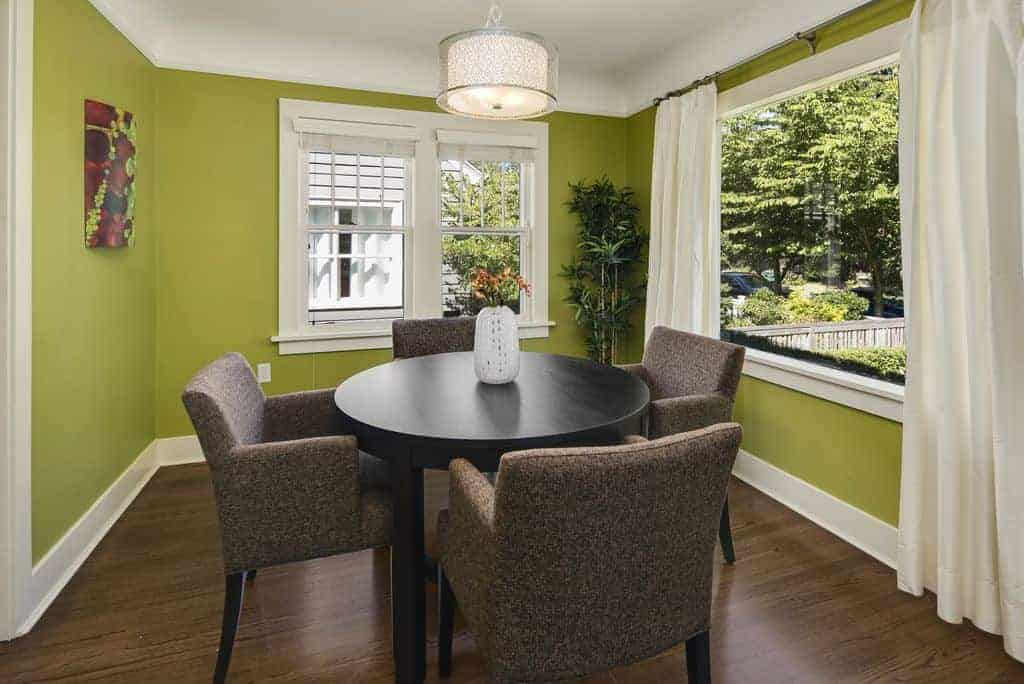 This small and simple green-walled dining room is given an airy demeanor by the windows that bring in natural light on the dark wooden circular table.