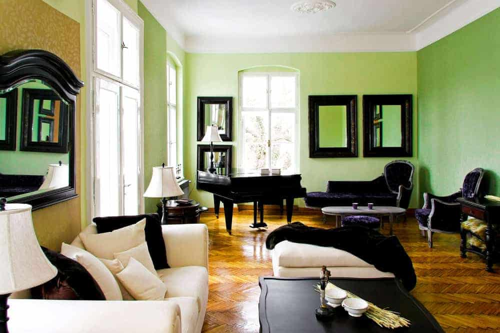 The light green walls are a nice contrast for the dark palette of the velvet cushioned chairs facing the dark grand piano by the corner illuminated by tall windows.