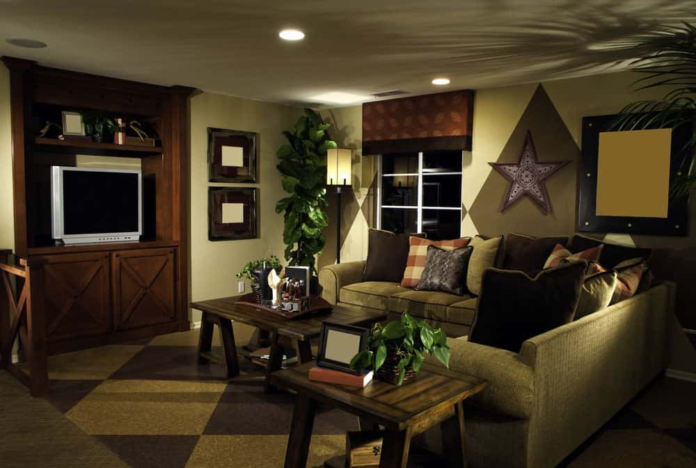 The light green walls are accented with large checkered patterns that reflect the checkered patterns of the brown carpeting of the floor that matches the L-shaped sofa and wooden TV housing.