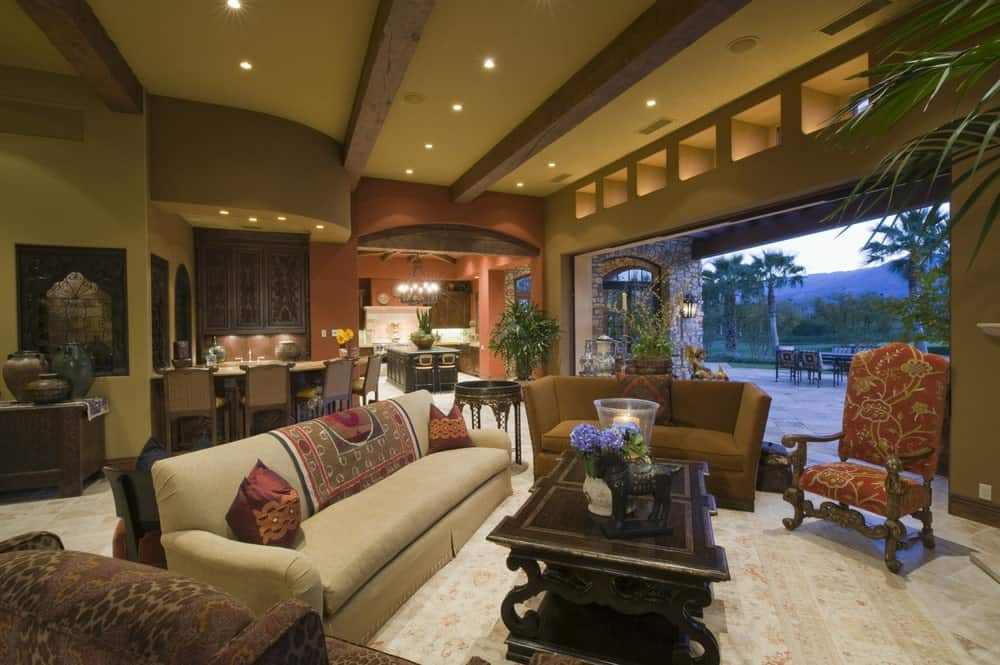 The walls and ceiling of this luxurious living room are given an earthy green palette that matches the exposed wooden beams of the ceiling and contrasts the white marble flooring topped with various couches and chairs.