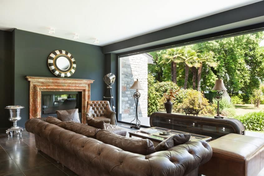 The dark green walls are well contrasted by the white ceiling and the massive glass wall featuring a lush garden outside. This is a nice background for the brown leather furniture and brown floor tiles of the living room.