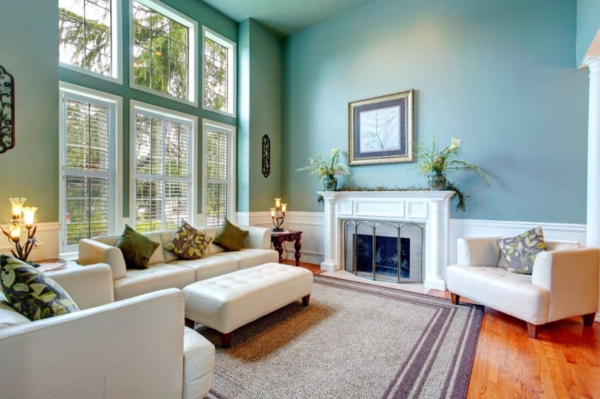 The bright pastel green hue of the walls and ceiling are paired with white elements of the leather cushioned sofa set and the fireplace inlaid with white finishing that blends with the wainscoting.