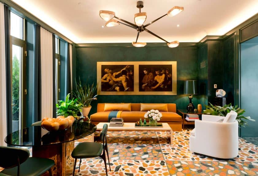 The dark sea-green walls are accented with classical paintings mounted over the yellow leather sofa that matches the yellow patterned tiles of the flooring.