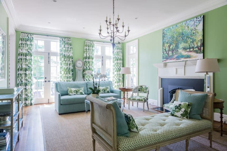 The green floral elements seen on the pillows, chair cushion and tall curtains framing the tall windows are a nice complement for the light green walls and sofa contrasted by the navy blue framing of the fireplace.