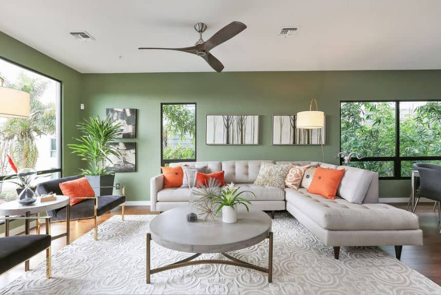 The tree silhouette artworks mounted on the green wall over the L-shaped sofa match the lush trees featured outside the windows that brighten up the white patterned area rug.