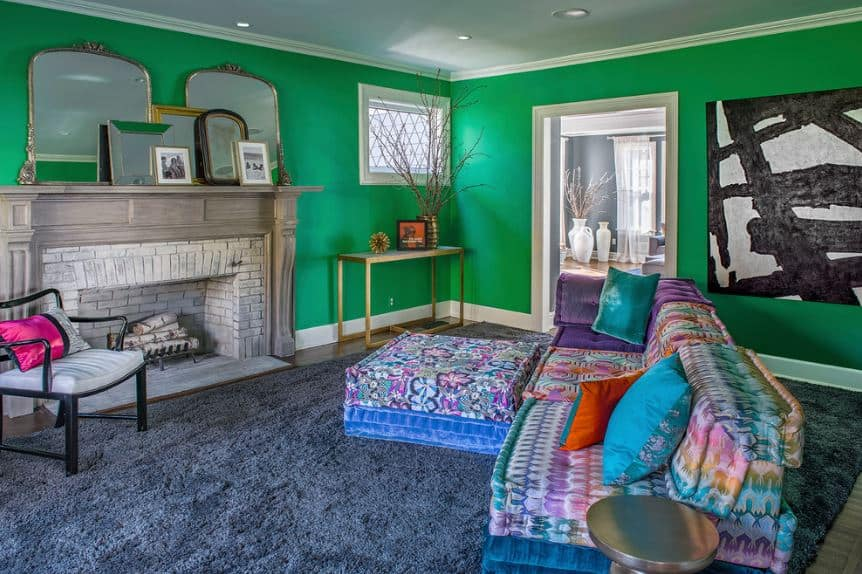 The crayon green color of the walls serves as a lighthearted background for the colorful L-shaped sofa over the furry blue area rug facing the gray fireplace.