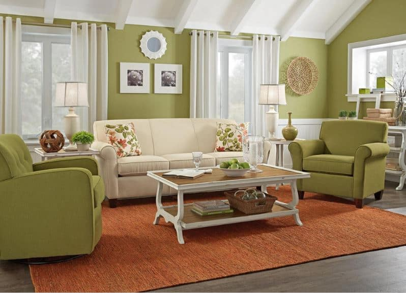 The wonderful avocado green walls are paired with a couple of avocado green armchairs that contrast the orange woven area rug with a white coffee table on it.