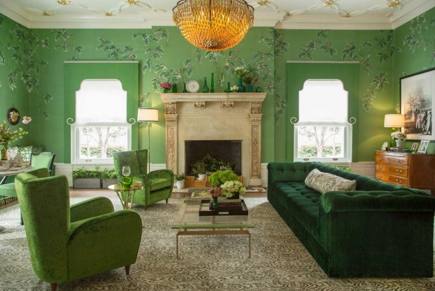 This is a chic living room with various shades of green adorned with floral elements on the walls, ceiling and as decorations in vases. The massive beige marble housing of the fireplace is a nice match for the dome-shaped lighting.