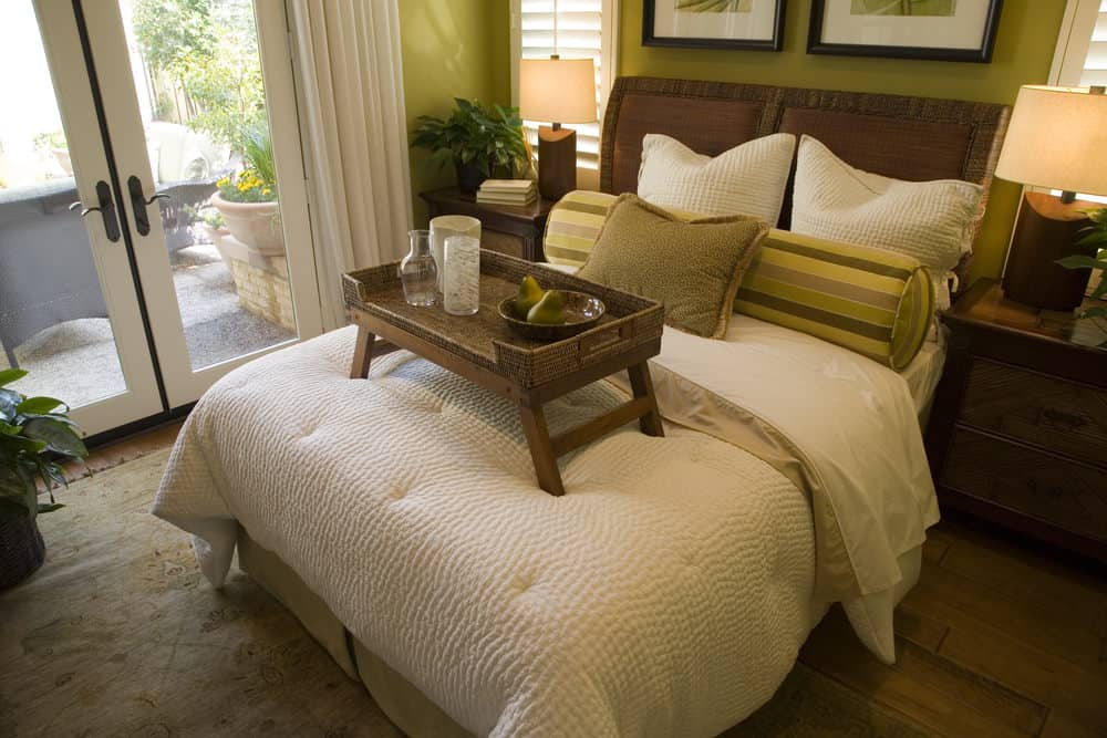 The yellow-green walls of this bedroom are brightened by the multiple sources of light surrounding the traditional bed flanked by wooden bedside drawers.
