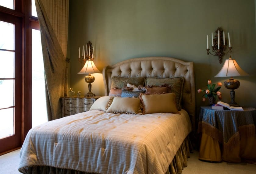 The charming bed has a brown cushioned headboard that is flanked with wall-mounted candelabras as an accent for the plain green wall.