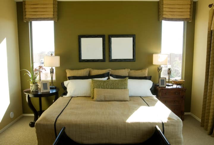 The head of the traditional bed has a green wall that is flanked by tall and narrow windows above a bedside table and drawer.