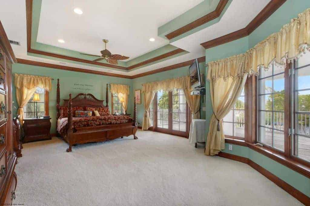 This spacious bedroom is dominated by a large pencil poster bed that matches the wooden molding of the green walls.