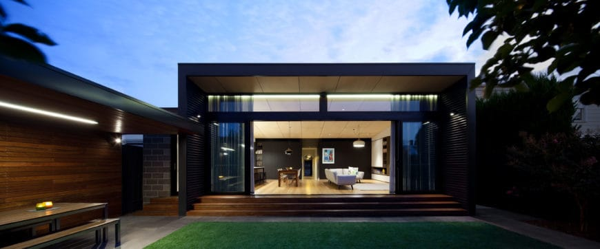 Modern house with a black exterior and a nice outdoor area with an outdoor dining.
