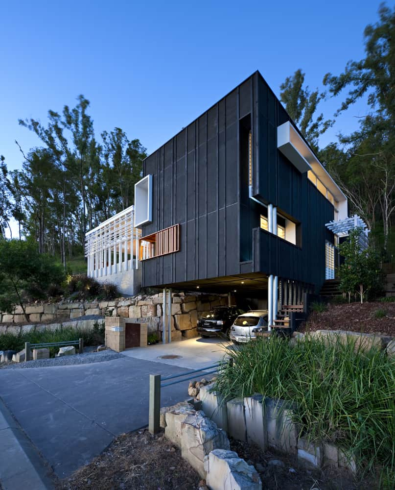 A contemporary home with a black and white exterior and has a wide garage that can fit two cars.