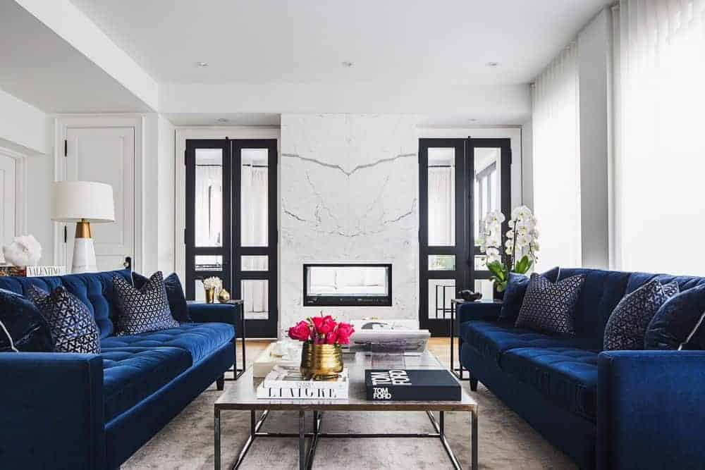 Transitional-style living room with a fireplace, a coffee table between blue sofas, and an area rug.
